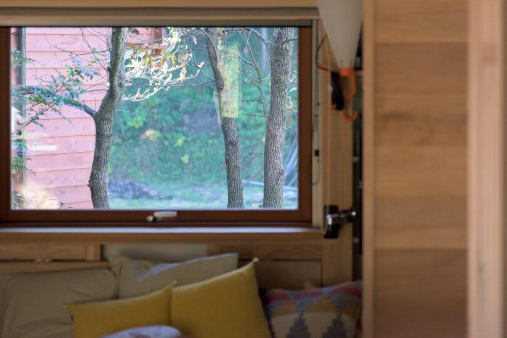 庭の木立とお隣の家の壁が見える西側の窓