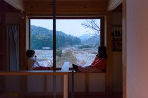 窓辺に腰かけて今朝の雪景色を眺める娘たち_シンケンスタイルの木の家